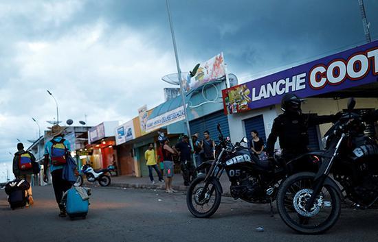 19日,巴西边境,防爆警察驻守,委内瑞拉难民(左)出示护照后通过。视觉中国 图