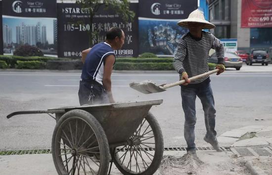 2018年5月2日,四川省绵竹市,吴加芳(右)正在一个小区的煤气管道改造工程上工作。新京报记者 尹亚飞 摄