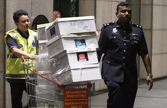 当地时间5月18日,马来西亚警方带走从前总理纳吉布住所搜出的箱子。