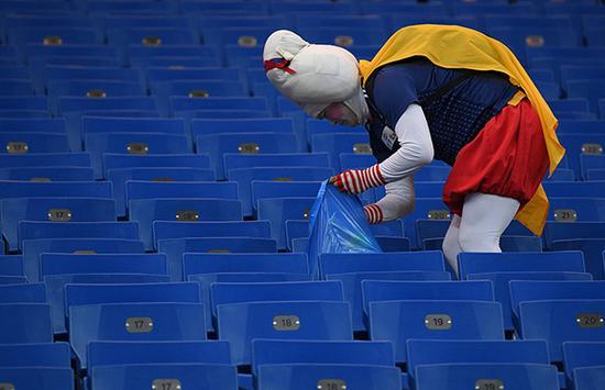 赛后正在清理垃圾的球迷。视觉中国 图
