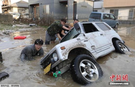 当地时间7月9日,日本冈山县仓敷市民众正在打捞被洪水围困的汽车。
