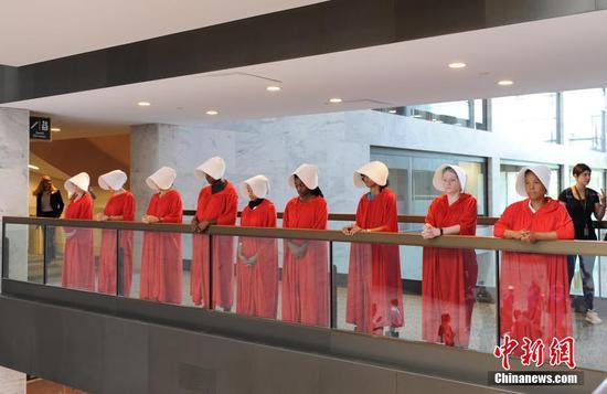 有民众身着美剧《使女的故事》人物服装在听证会大厅抗议。图自中新网
