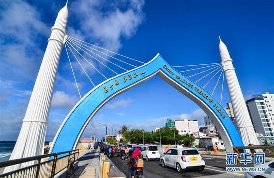 2018年10月2日,车辆从由中国援建、连接马尔代夫首都马累和机场岛的中马友谊大桥桥头拱门穿过。 新华社发(杜才良 摄)