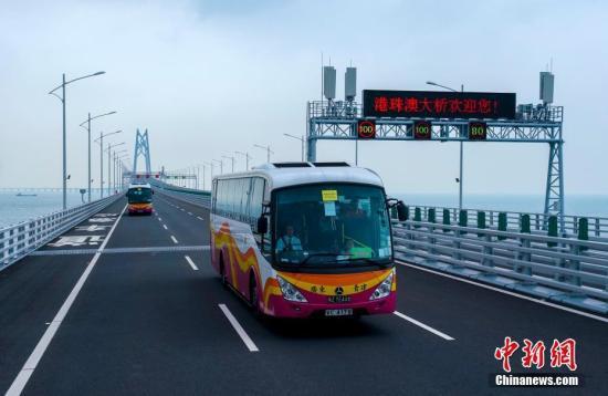 10月24日,大巴车经过港珠澳大桥青州航道桥附近。中新社记者 张炜 摄