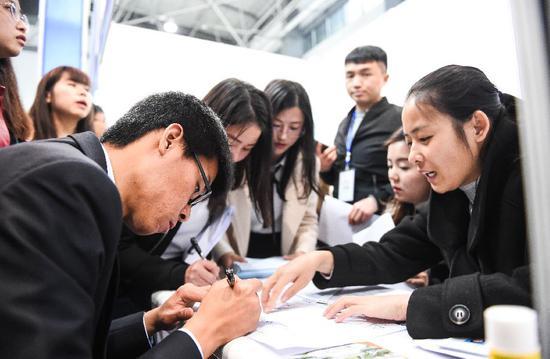 ▲3月24日,第六届中国贵州人才博览会开幕,求职者现场填写求职申请。  图/新华社