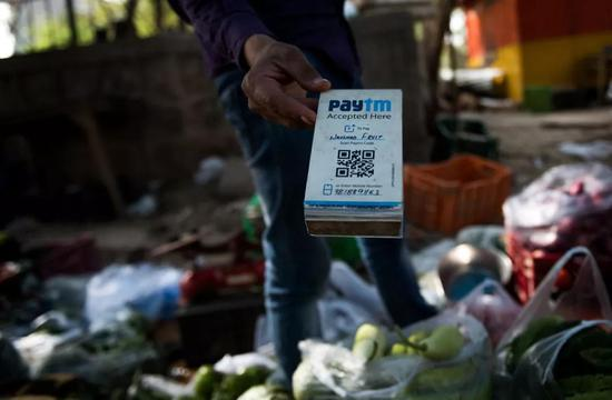 2018-07-23,在印度新德里街头,一名蔬菜摊主手持Paytm二维码接受电子支付。印度Paytm在支付宝母公司蚂蚁金服的支持下,已经成为印度最大的移动支付平台。新华社记者毕晓洋摄