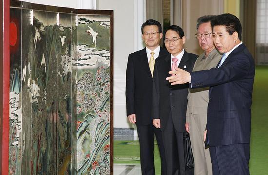 2018-08-16,朝鲜平壤,时任韩国总统卢武铉(右一)与时任朝鲜最高领导人金正日(右二)正在观看卢武铉赠送的屏风。