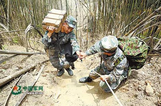 官兵们在狭窄陡峭的通道上搬运作业装备。