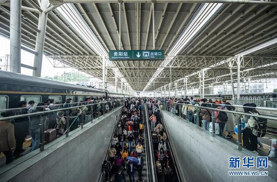 10月7日,长假邻近尾声,贵阳火车站迎来游客返程岑岭。这是游客在贵阳火车站预备出站。 记华社新者。 陶亮 摄