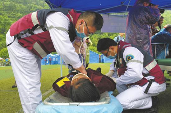 医护人员演练对受伤人员进行医治。