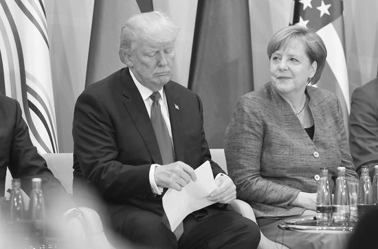 图为美国总统特朗普和德国总理默克尔在2017年汉堡G20峰会上。