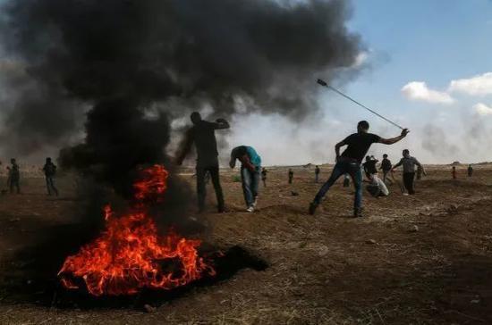 5月11日,在加沙地带东部与以色列接壤的边境地区,巴勒斯坦示威者向以色列士兵投掷石块。新华社发