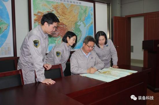 ▲江晓华高工正在和同事讨论工作。