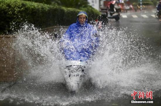 8月17日,南京街头的一名男子骑车从积水中冲过。泱波 摄