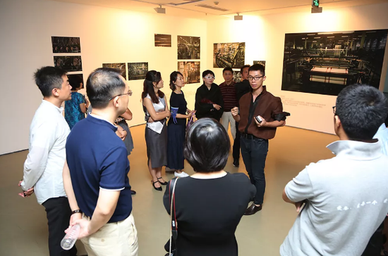 嘉宾及观众聚集在艺术家江凯群周围,聆听艺术家本人的讲解。