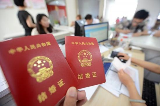 资料图片:新人在江苏扬州市广陵区民政局展示刚领取的结婚证。(2013年8月13日摄)新华社发