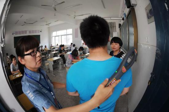 △2015年安徽亳州市二中考点,监考老师正在用金属探测仪对考生进行检查。/视觉中国