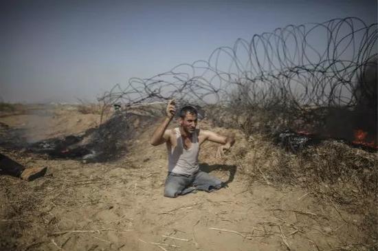5月11日,在加沙地带东部与以色列接壤的边境地区,一名双腿残疾的巴勒斯坦示威者向以色列士兵投掷石块。