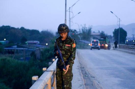 5月12日,一名民兵在缅甸木姐的一座桥上执勤。(法新社)