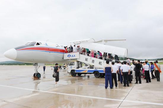 资料图:赴朝鲜旅游的游客登机。 新华社发