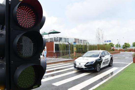 资料图:智慧小镇中一辆自动驾驶的车辆在辨识红绿灯后通过。 新华社记者 唐奕 摄