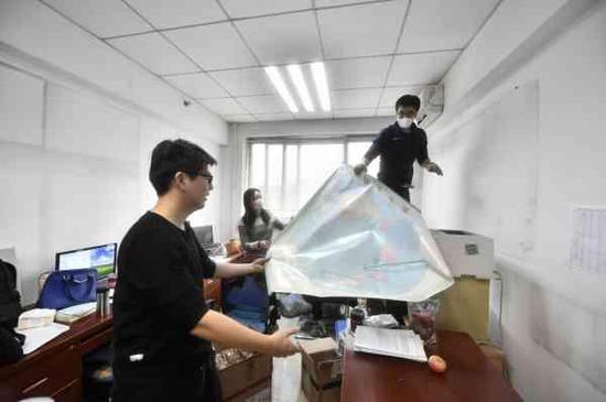 2018年12月21日,在北京市人民政府外事办公室,工作人员摘下世界地图打包运抵北京城市副中心行政办公区。北京日报客户端记者蔡代征摄