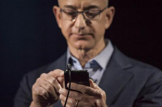 """资料图:亚马逊公司首席执行官杰夫·贝索斯展示亚马逊发布的第一款智能手机""""Fire Phone""""。 (新华社)"""