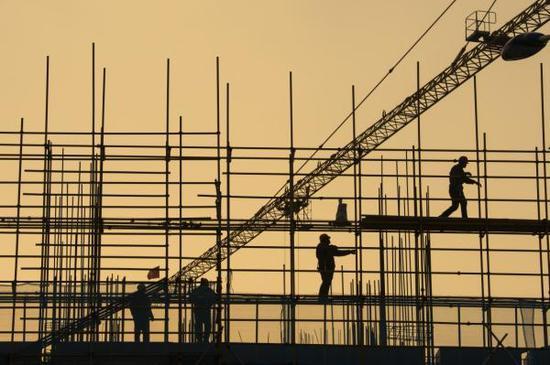 2019年1月1日,在江苏省海安市一建筑工地,工人在脚手架上作业。新华社 图
