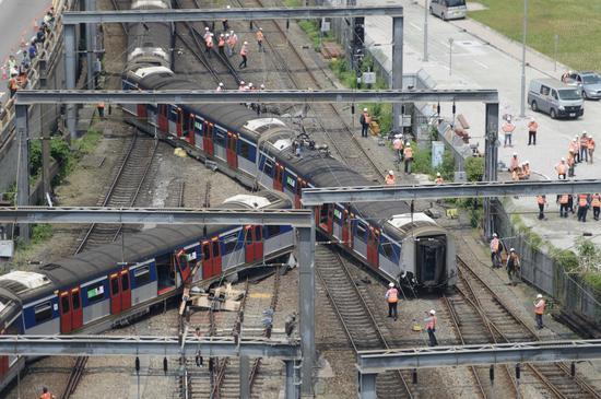 出轨列车停在铁轨上,多名工作人员在现场处置。 新京报特派香港报道组 摄