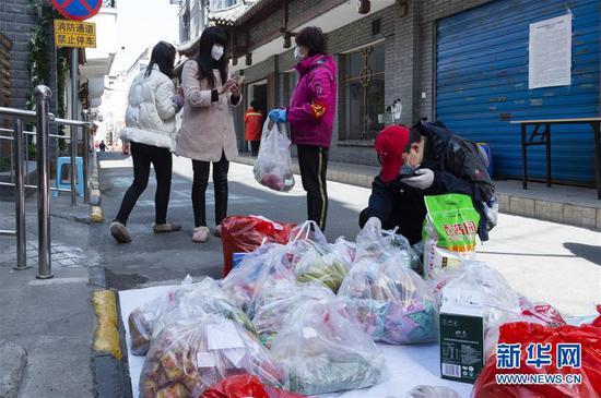 3月15日,湖北省襄阳市水星台社区党委书记刘晓琳(右二)和社区事情职员在检察、分发住民从网上订购的生涯用品。 新华社发(谢剑飞 摄)