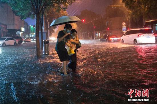 资料图:8月9日晚,北京市民冒雨涉水出行。当日,北京气象台发布18时至23时降水量(毫米):全市平均17.9,城区平均28.1。 中新社记者 田雨昊 摄