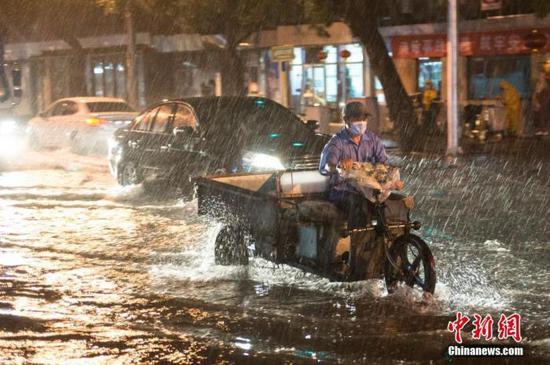 资料图:8月9日晚,北京市民冒雨涉水出行。当日,北京气象台发布18时至23时降水量(毫米):全市平均17.9,城区平均28.1。大部地区出现7、8级阵风,局地达9到11级。 中新社记者 田雨昊 摄