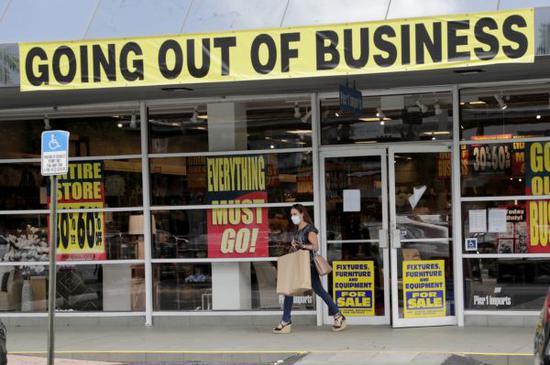 顾客走出一家在新冠疫情重压下即将歇业的商店(美联社)