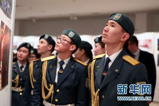 """▲""""今日中国暨国防和军队建设""""发展成就图片展在哈萨克斯坦阿斯塔纳举行。哈萨克斯坦军校学生观看展览。"""
