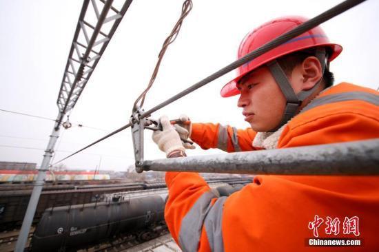 """资料图:电气化铁路""""接触网""""技术工人们,被称作铁路""""蜘蛛侠""""。 中新社记者 王舒 摄"""