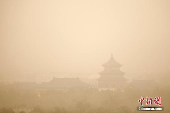 """3月28日,雾霾沙尘齐聚京城,除此前启动的空气重污染橙色预警之外,官方还发布了今年首个沙尘蓝色预警。在两者""""夹攻""""之下,全城空气质量已达到严重污染水平。 中新社记者 富田 摄"""