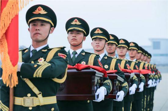 3月28日,在韩国仁川国际机场,中方礼兵护送志愿军烈士遗骸上飞机。(新华社)