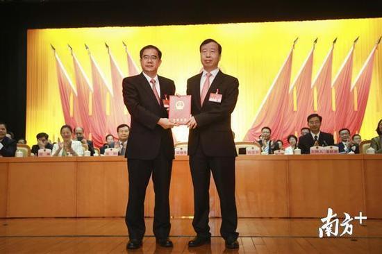东莞市委书记、市人大常委会主任梁维东为新当选的东莞市人民政府市长肖亚非颁发当选证书。