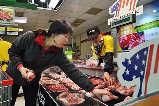 河南郑州的一位消费者正在超市挑选从美国进口的猪肉。图片来源:中国日报
