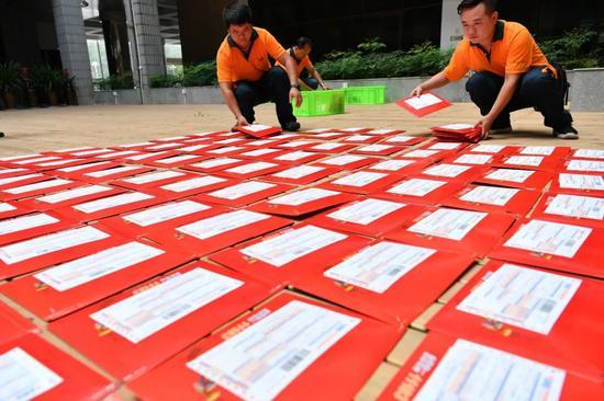 △2017年7月25日,云南邮政工作人员把录取通知书逐一装箱带走。/视觉中国