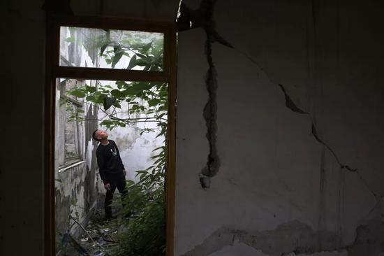 2018年5月1日,四川省绵竹市兴隆镇广平村,吴加芳在老宅里查看。这里是他和亡妻一起生活过的地方。新京报记者 尹亚飞 摄