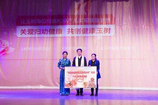 林风会长为玉树州妇女联合会主席白马求吉、玉树市副市长才仁永吉传递项目爱心牌。