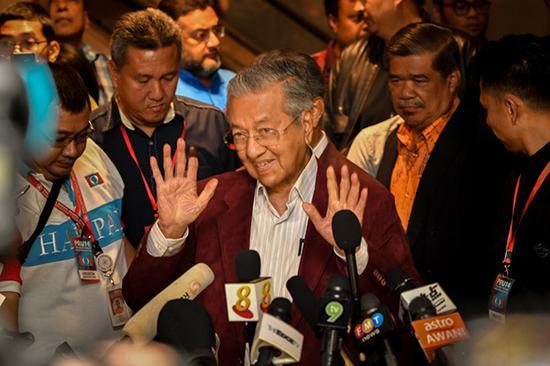 5月10日,在马来西亚必打灵查亚,马哈蒂尔(中)出席新闻发布会。马来西亚选举委员会10日公布的计票结果显示,前总理马哈蒂尔领导的反对党阵营在9日举行的大选中赢得国会下议院过半数席位。新华社发(张纹综摄)