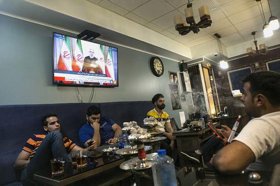 5月8日,在伊朗首都德黑兰,人们观看伊朗总统鲁哈尼的电视讲话。伊朗总统鲁哈尼8日晚发表电视讲话说,虽然美国决定退出伊核协议,但伊朗将暂时留在伊核协议中并将与协议其他各方磋商。新华社发(哈拉比萨兹摄)