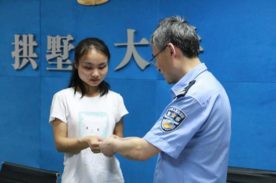 秦女士女儿从民警手中接过身份证。 本文图片均为拱墅公安提供