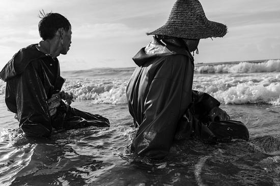 坐在海边稍作休息的渔民
