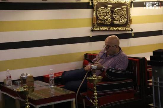 独自在饭店里抽着水烟的商人。