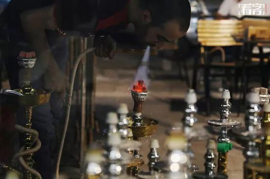 路过一家中东餐厅时,叙利亚小伙默罕默德正在吹旺水烟的炭火。默罕默德来中国已经三年了,在义乌开有一家理发店,最近由于店面搬迁有了些空档时间,默罕默德便到一家餐厅打工,专门负责给客人们点水烟挣些外快,多的时候一晚上能卖40多支,一支卖30元人民币。