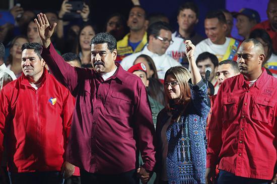当地时间2018年5月20日,委内瑞拉现任总统马杜罗在大选获胜后,携妻子在总统官邸向支持者发表讲话,并挥手致意。 东方IC 图