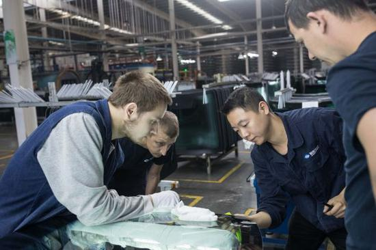 2017年7月,在位于俄罗斯卡卢加的福耀玻璃俄罗斯有限公司,中国员工为当地员工讲解玻璃检验方法。(吴壮 摄)